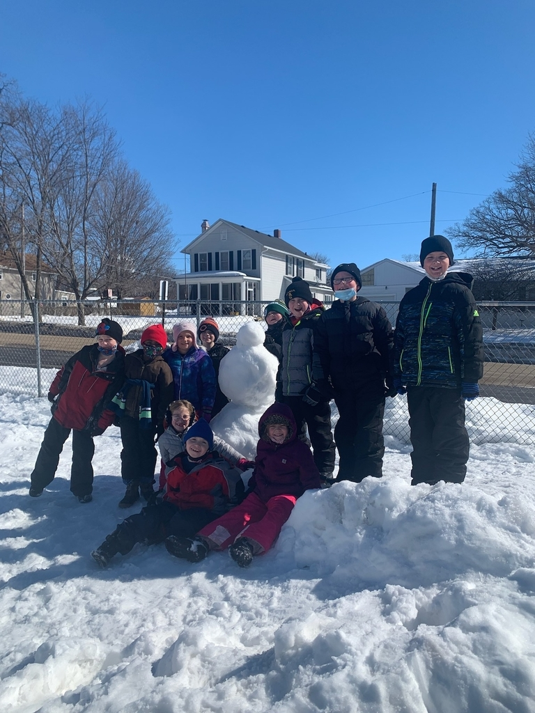 Second graders build a snowman as they enjoy a beautiful day at recess.