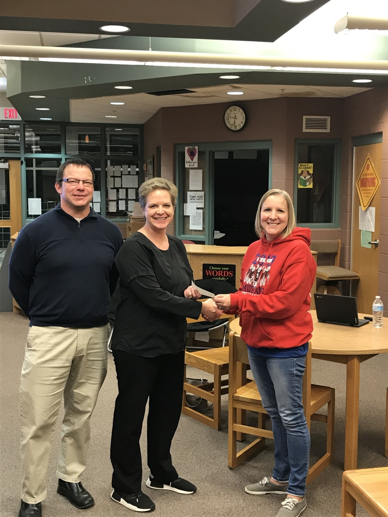 Amy Swaim and Joe Robbins present board president Cathleen Vegter a check for the MCUD #6 libraries.